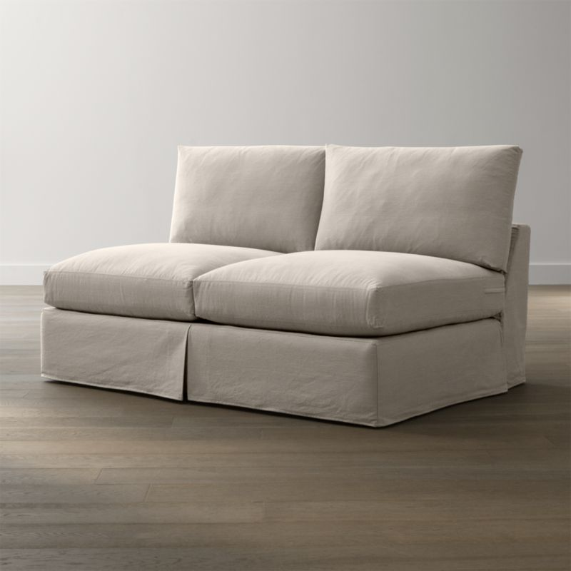 """Tailored to fit our Lounge Slipcovered Armless Loveseat, smart denim slipcover is tailored with a kickpleat skirt and jumbo double topstitch outlining its plump, deep cushions.<br /><br />Additional <a href=""""http://crateandbarrel.custhelp.com/cgi-bin/crateandbarrel.cfg/php/enduser/crate_answer.php?popup=-1&p_faqid=125&p_sid=DMUxFvPi"""">slipcovers</a> available below and through stores featuring our Furniture Collection.<br /><br />After you place your order, we will send a fabric swatch via next day air for your final approval. We will contact you to verify both your receipt and approval of the fabric swatch before finalizing your order.<br /><br /><NEWTAG/><ul><li>100% cotton</li><li>Machine washable</li><li>Jumbo contrast saddle stitch detail</li><li>Made in North Carolina, USA of domestic and imported materials</li></ul><br />"""