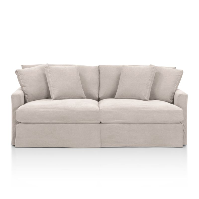 """A Casual Friday dress code for our popular, laid-back Lounge Collection. Smart dove grey denim slipcover is tailored with a kickpleat skirt and matching jumbo double topstitch outlining its high, slim arms and plump, deep cushions.<br /><br />Additional <a href=""""http://crateandbarrel.custhelp.com/cgi-bin/crateandbarrel.cfg/php/enduser/crate_answer.php?popup=-1&p_faqid=125&p_sid=DMUxFvPi"""">slipcovers</a> available below and through stores featuring our Furniture Collection.<br /><br />After you place your order, we will send a fabric swatch via next day air for your final approval. We will contact you to verify both your receipt and approval of the fabric swatch before finalizing your order.<br /><br /><NEWTAG/><ul><li>Eco-friendly construction</li><li>Certified sustainable, kiln-dried hardwood frame</li><li>Seat cushions are multi-layer soy- or plant-based poly foam wrapped in fiber down blend and encased in downproof ticking</li><li>Back cushions are fiber down in downproof ticking</li><li>100% cotton slipcover</li><li>Removable slipcovers are machine washable</li><li>Jumbo contrast topstitching detail</li><li>Flexolator spring suspension</li><li>Benchmade</li><li>Made in North Carolina, USA of domestic and imported materials</li></ul>"""