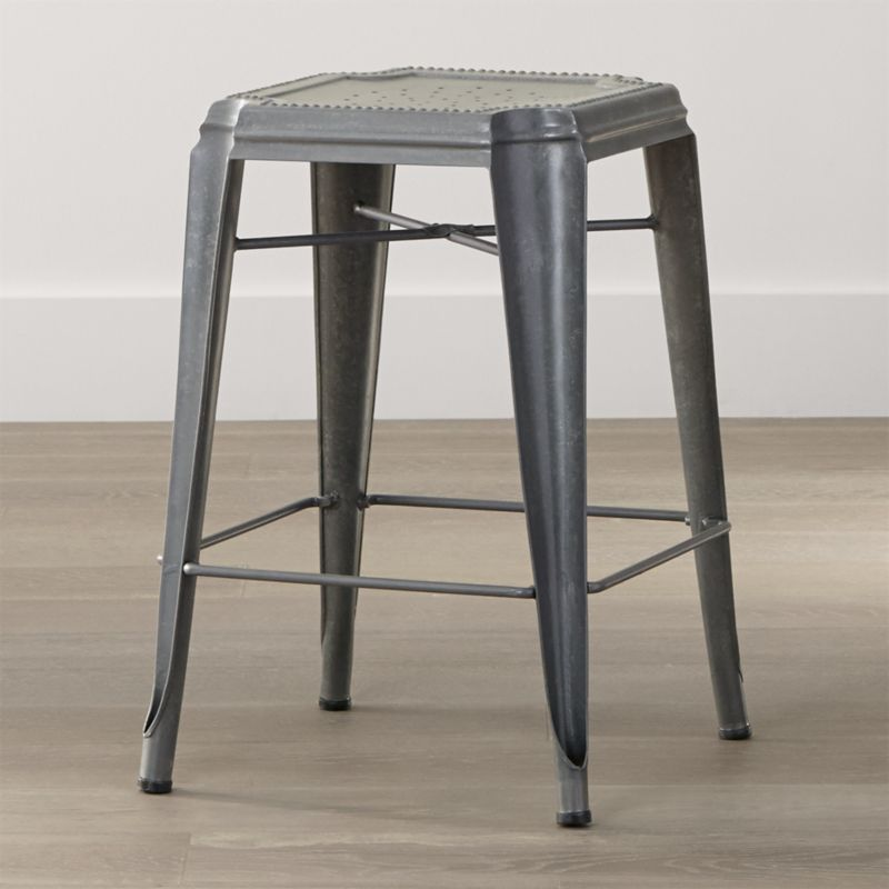 With its decorative seat, unique reverse-arched legs and hand-distressed finish, our Lyle backless stool is the perfect perch for counter and extra high-dining seating in eclectic spaces, indoors or out. Crafted of steel with a galvanized finish, this backless stool shows off artful details that lend it all the charm and character of a flea market find. <NEWTAG/><ul><li>Die cut and welded galvanized steel sheet with clear powdercoat finish</li><li>Stack up to four high</li><li>Plastic glides</li><li>Made in India</li></ul>