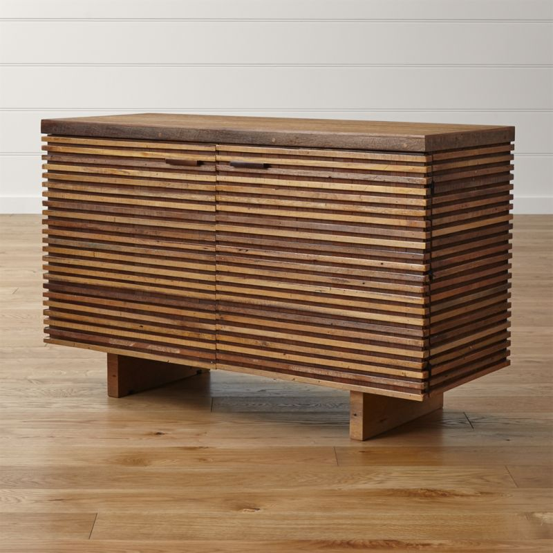 Telling a story of timber reclamation from around the world, the Paloma II small sideboard offers modern dining storage with a rich history and a beautiful range of natural wood grains in dark and honeyed browns. The small sideboard's distinctive base of precision-cut strips is handcrafted of peroba wood reclaimed from homes in Brazil no longer in use, with the striking front hand-assembled in a horizontal Prairie-style continuum. <NEWTAG/><ul><li>Reclaimed peroba wood case</li><li>Reclaimed Australian hardwood top</li><li>Clear water-based lacquer finish</li><li>Each piece is unique due to the natural aging process of the reclaimed woods</li><li>2 drawers with metal glides and 1 adjustable shelf</li><li>Leg levelers</li><li>Cord management cutouts</li><li>Made in Indonesia</li></ul><br />