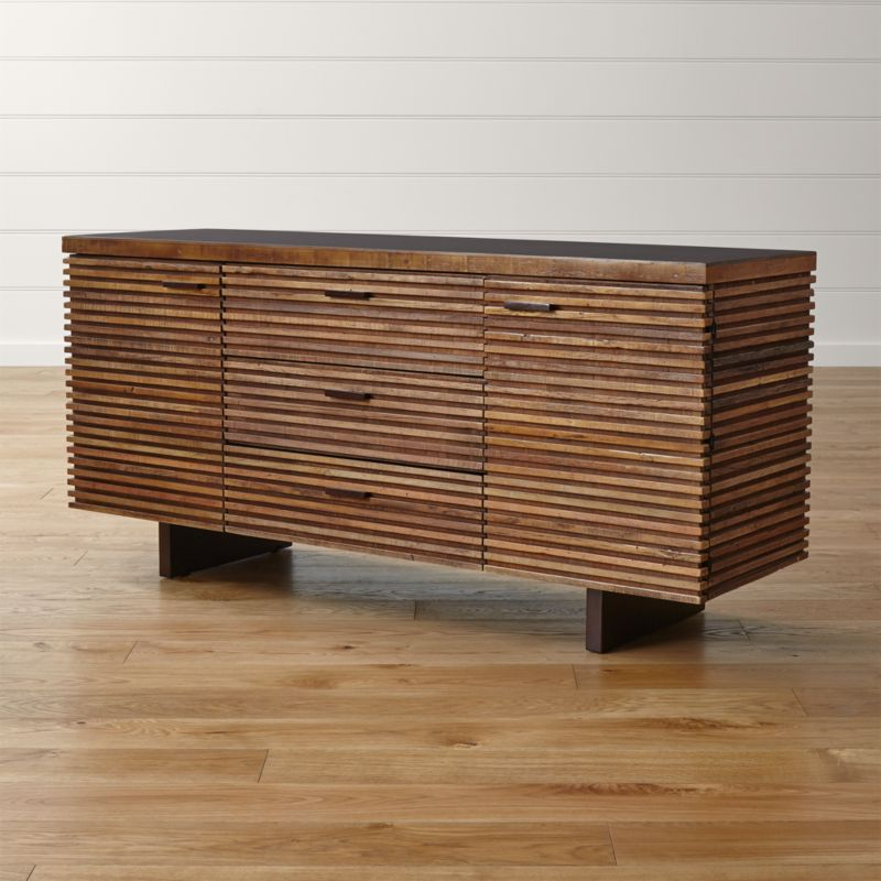 Rare and exotic peroba wood is reclaimed and artfully repurposed in this Zen-meets-Prairie-Style dining storage option. The wood is salvaged from the siding and floors of old buildings in Brazil no longer in use, then restored and handcrafted to create the The Paloma I large sideboard's dynamic presence. <NEWTAG/><ul><li>Reclaimed peroba wood, engineered wood and mahogany veneer</li><li>Java brown finish with water-based clear lacquer topcoat on top and drawer pulls</li><li>Each piece is unique due to the natural aging process of peroba wood</li><li>3 drawers and 2 doors with solid mahogany pulls</li><li>4 adjustable shelves</li><li>Metal glides</li><li>Leg levelers</li><li>Cord management cutouts</li><li>Made in Indonesia</li></ul><br />