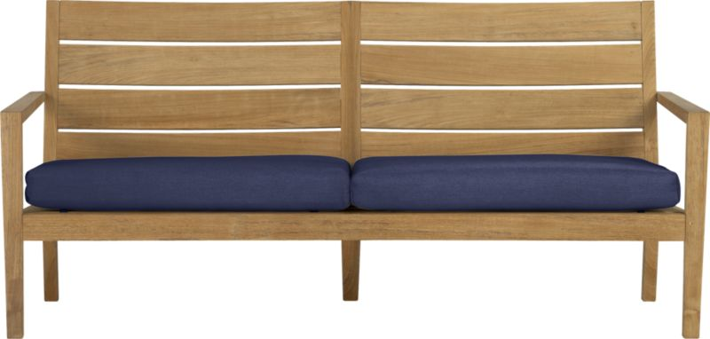 Our eco-friendly Regatta teak lounge collection cuts a clean, classic profile in a bold wide-slat design. Relax on a full-size sofa with sleek arms and comfortable angled backs. All pieces are handcrafted of plantation-grown teak supported by the TFT, a nonprofit organization that promotes responsible forest conservation. We recommend allowing the unfinished teak to weather to a silvery grey. To maintain the natural color, use our Golden Care® Teak Protector. Cushions are fade- and mildew-resistant Sunbrella acrylic in deep indigo blue. Regatta dining collection also available.<br />After you place your order, we will send a fabric swatch via next day air for your final approval. We will contact you to verify both your receipt and approval of the fabric swatch before finalizing your order.<br /><br /><NEWTAG/><ul><li>Solid teak harvested from plantations working with TFT</li><li>Unfinished</li><li>Mortise-and-tenon joinery</li><li>Stainless steel hardware</li><li>Cushion is fade- and mildew-resistant Sunbrella acrylic</li><li>Polyester batting and foam cushion fill</li><li>Cushion is secured with fabric tab fasteners</li><li>Spot clean the cushion cover</li></ul>