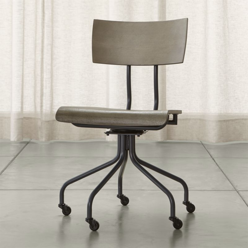 Subtle curves and a linear frame makes a study of the school desk chair of yesteryear in this updated silhouette. Warmly pairing neutral grey-toned stain paired with industrial metal, this versatile, affordable seat easily rolls on casters and swivels 360 degrees. <NEWTAG/><ul><li>Designed by Mark Daniel of Slate</li><li>Metal frame and legs</li><li>Poplar core seat and back with engineered bentwood and ash veneer</li><li>360 degree swivel mechanism</li><li>Decorative, non-adjusting knob</li><li>Metal and plaster casters</li><li>Made in China</li></ul><br />