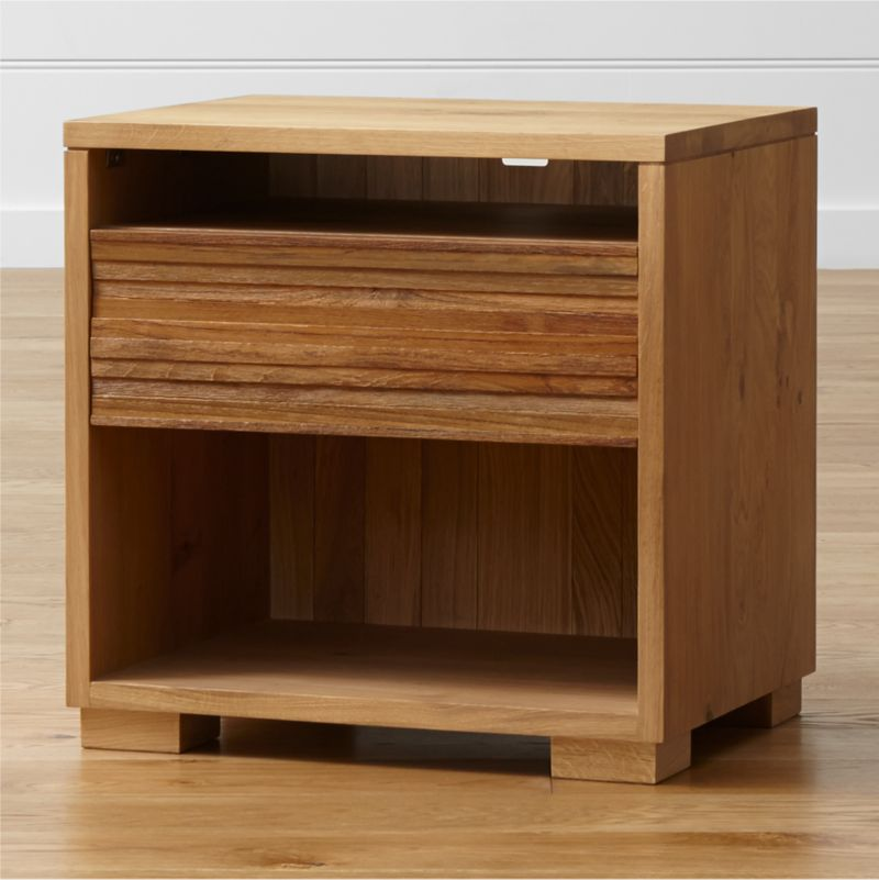 An unexpected, contemporary nightstand design shapes up in an eco-friendly union of repurposed teak and solid European white oak. Comprising a top shelf, two open spaces (one with cord cutout) and a convenient storage drawer, the Sierra nightstands rich texture is created by steel-brushing strips of repurposed teak, salvaged from spare production materials to highlight the grain's tone and texture. <NEWTAG/><ul><li>Solid European white oak frame finished with oil and wax</li><li>Solid, steel-brushed repurposed teak finished with clear topcoat</li><li>As with all solid woods, expansion and contraction may occur with seasonal changes in humidity</li><li>Tongue-and-groove joinery</li><li>1 drawer with integrated pull</li><li>Undermount metal drawer glides</li><li>Cord management cutout</li><li>Made in Vietnam</li></ul>