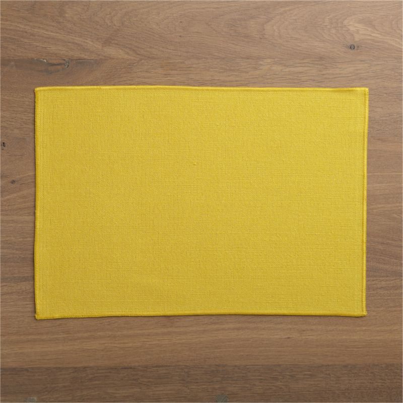 Surged edges give this no-fuss, solid yellow placemat a clean finish.<br /><br /><NEWTAG/><ul><li>62% linen and 38% cotton</li><li>Machine wash cold, line dry; warm iron as needed</li><li>Oversized to allow for shrinkage</li><li>Made in India</li></ul>
