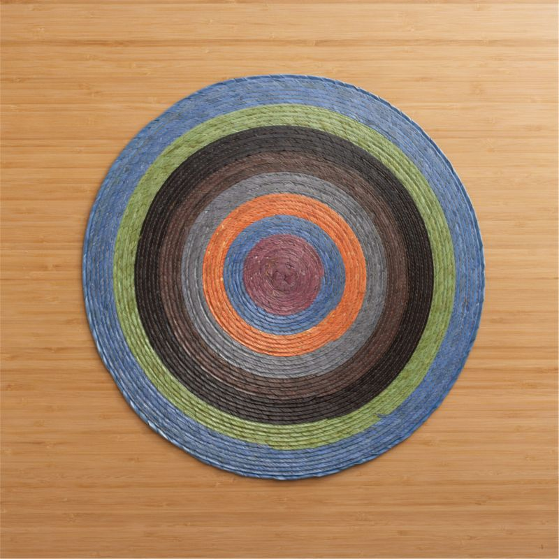 Colorful round radiates richly hued circles, handmade from natural Mexican palm and sealed with a wax finish for easy cleanup.<br /><br /><NEWTAG/><ul><li>100% palm fiber</li><li>Clean with a damp cloth</li></ul>
