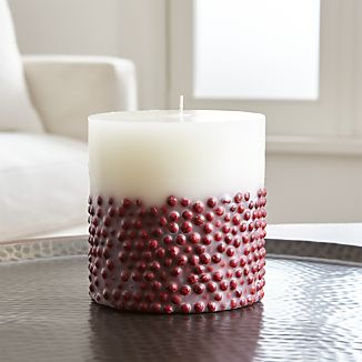 Red beads make like winter berries, embedded in a white pillar candle scented with the rich, warming scent of vanilla.