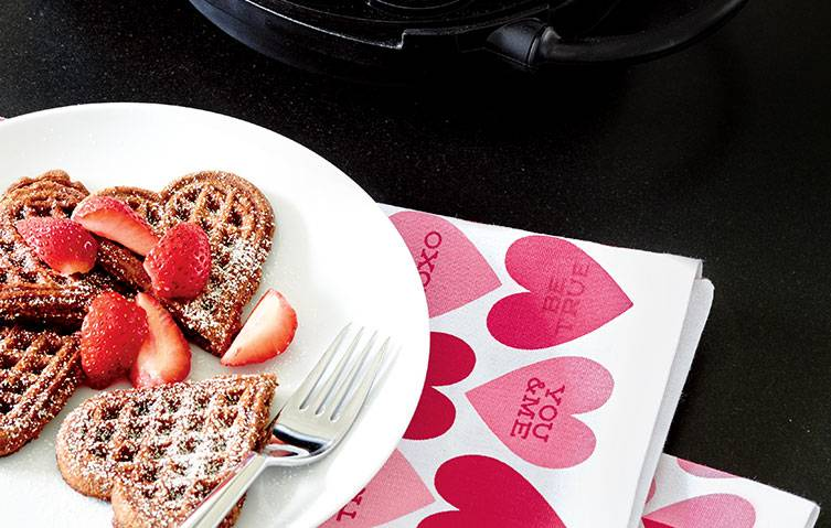 heart-shaped waffles and strawberries on white plates resting on heart-print dish towels.