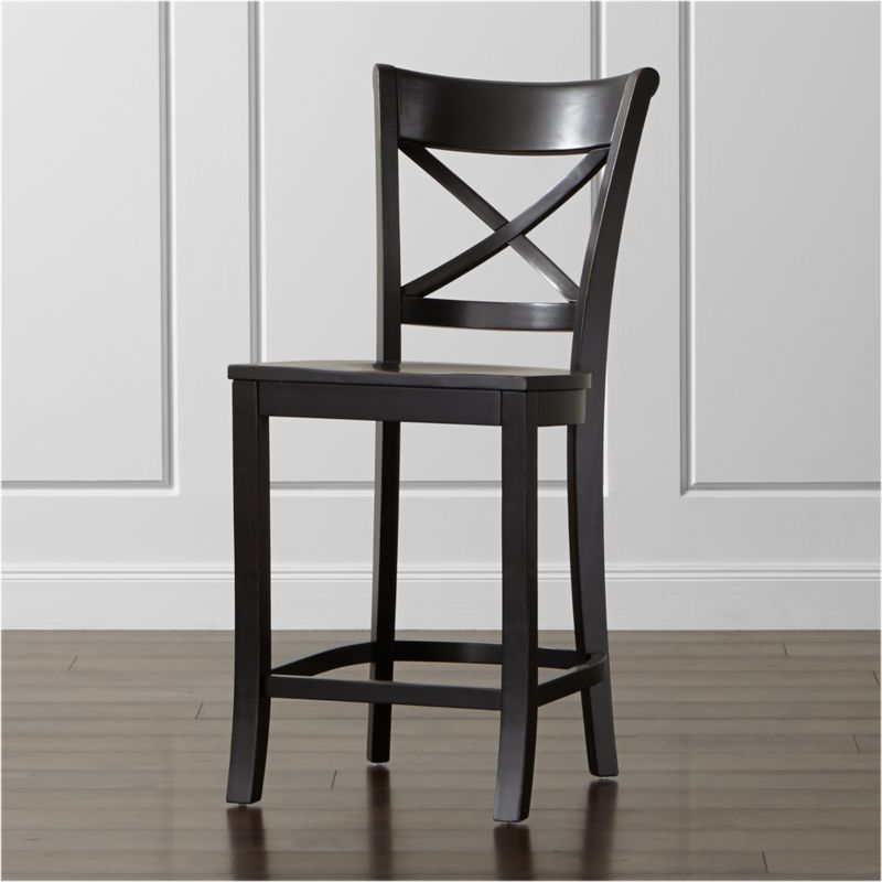 "Vintner's contoured ""X"" back and comfortable, carved seat support you in all the right places. This substantial farmhouse-style counter stool is crafted of solid wood with a black-painted finish that's hand-rubbed at the edges. <NEWTAG/><ul><li>Sustainable solid hardwood</li><li>Black-painted, antiqued and hand-rubbed finish with red undertones and clear lacquer topcoat</li><li>Made in Vietnam</li></ul>"
