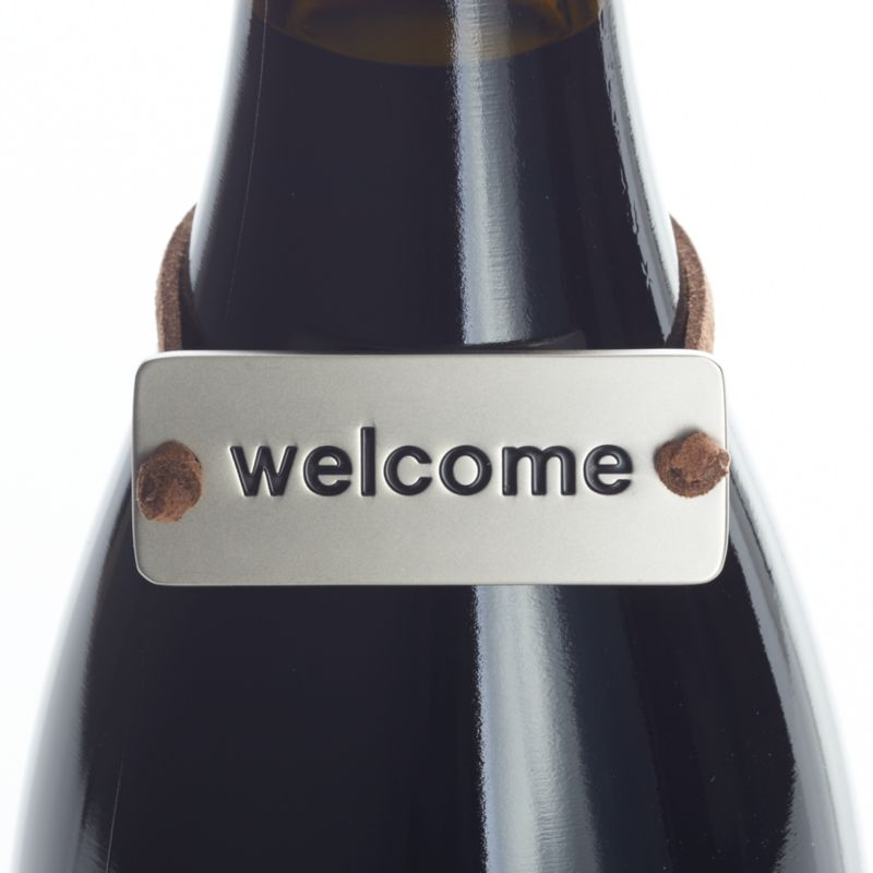 "Neat metal tag on a faux leather cord slips neatly over a gift bottle of wine, embossed to say a simple ""welcome.""<br /><br /><NEWTAG/><ul><li>Zinc with matte nickel plating</li><li>Faux leather cord</li><li>Clean with damp cloth</li><li>Made in China</li></ul>"