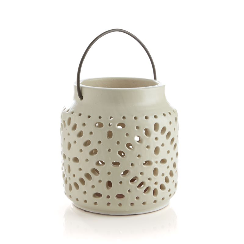 "Candlelight flickers through lace-patterned pores for modern mood lighting with a folk-art feel. Cool ivory ceramic looks great on a floor, tabletop or hanging from its iron loop handle.  Stage with Wisteria's different sizes and colors for an illuminating presentation indoors or out.<br /><br /><NEWTAG/><ul><li>Ceramic with iron handle</li><li>For indoor and outdoor use</li><li>Accommodates up to 3""-dia. pillar candle, sold separately</li><li>Dust with soft dry cloth</li><li>Made in China</li></ul>"