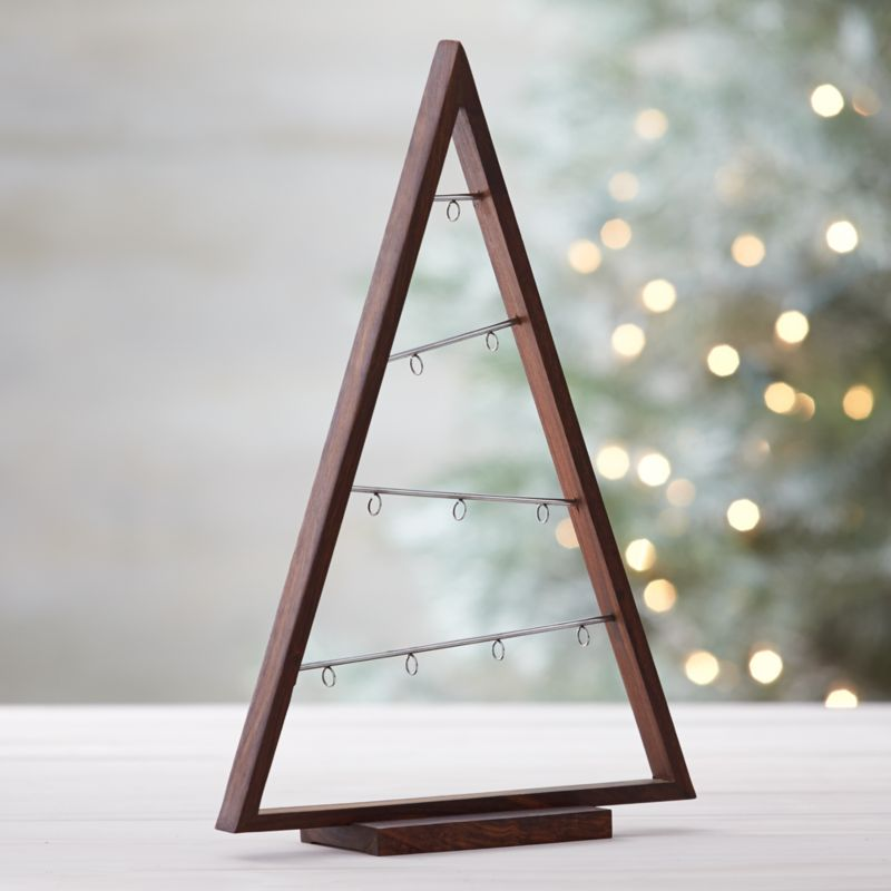 A simply styled triangle of natural shesham wood features diagonal metal bars with hooks to dangle a collection of ornaments in an implied tree shape.<br /><br /><NEWTAG/><ul><li>Wood and metal</li><li>Natural oil finish</li><li>Clean with a dry cloth</li><li>Made in India</li></ul>