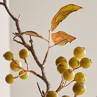 Golden berries and a few leaves ornament a single autumnal branch. Naturalistic detail brings a bit of fall to indoor arrangements.