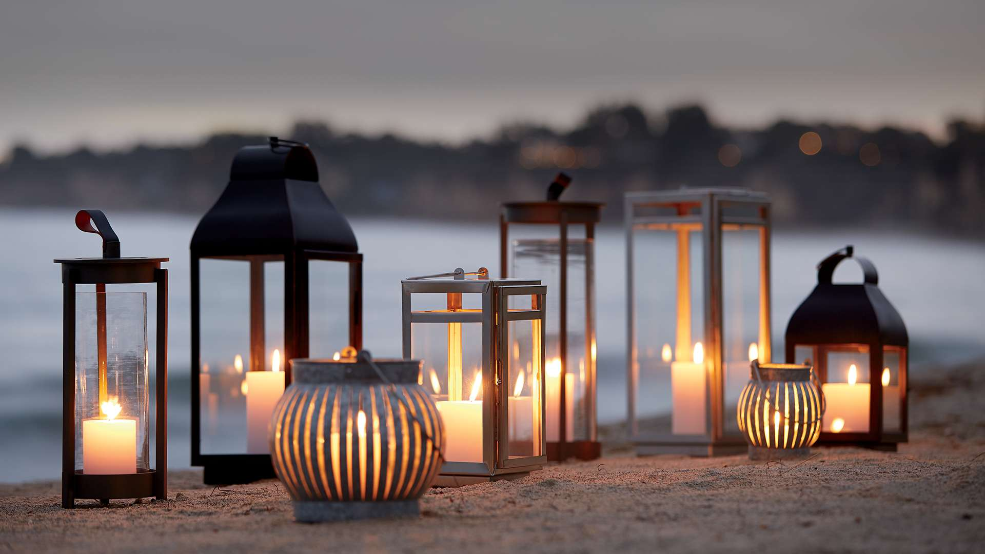Outdoor Lanterns and Candle Holders lit on a beach
