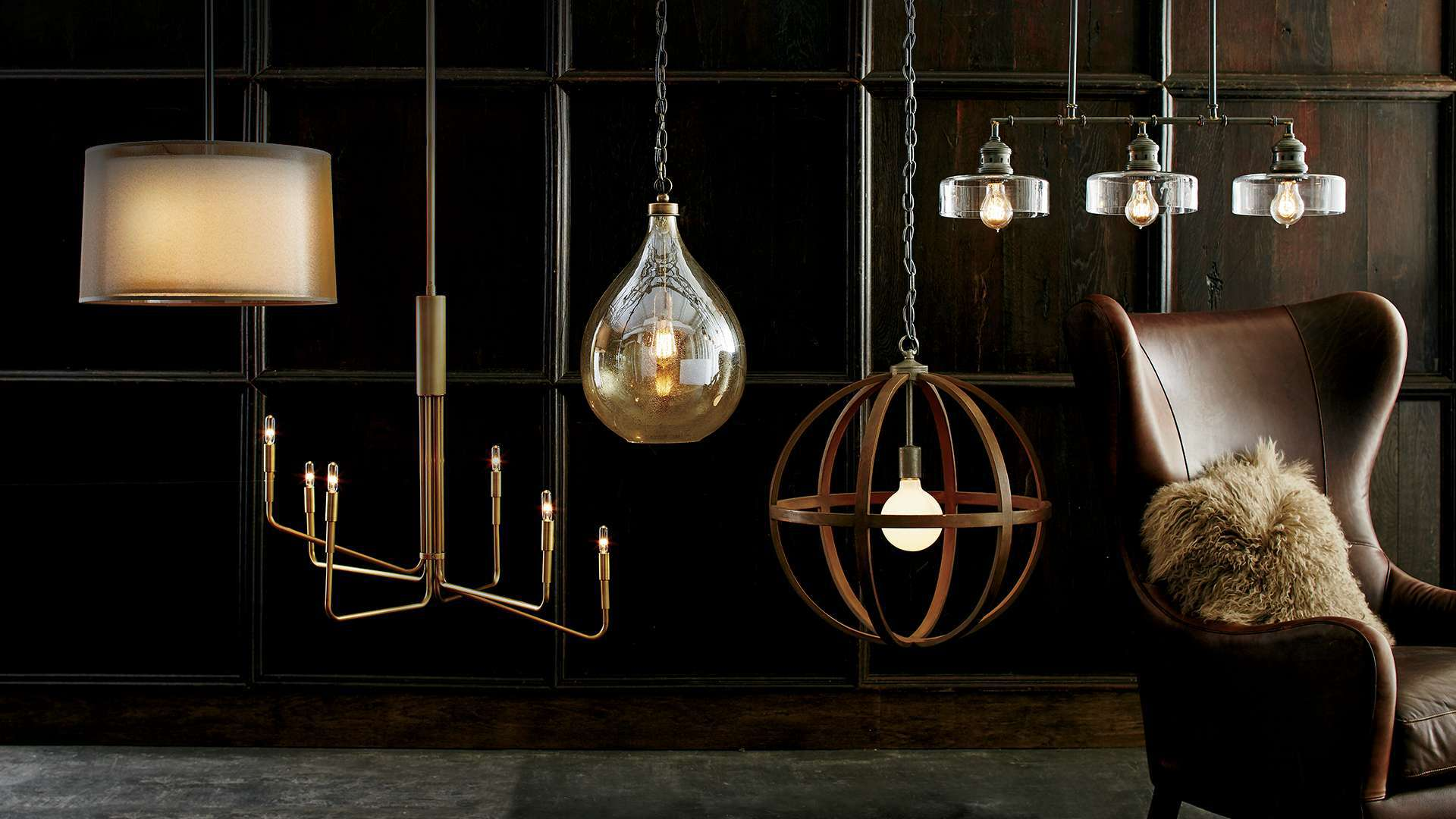 Multiple pendant lights hanging in a room with a leather chair