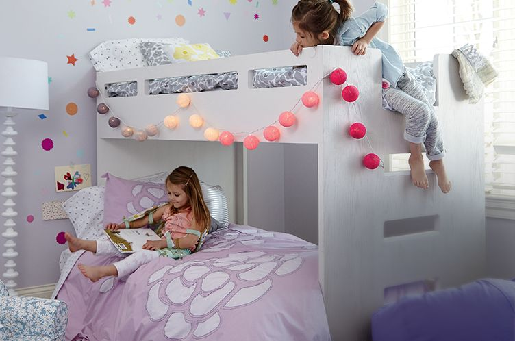 Two little girls playing on bunk beds