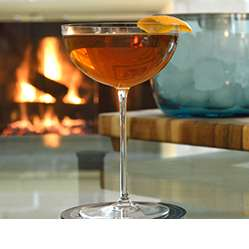 Camille Coup Chamagne Glass with a dark cocktail in it on a table in front of a fireplace