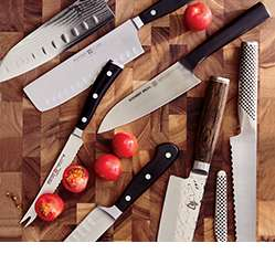 Different knives laid out on a cutting board