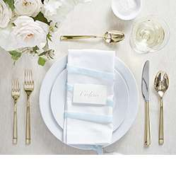 Formal dinner table setting with white dinnerware and gold flatware