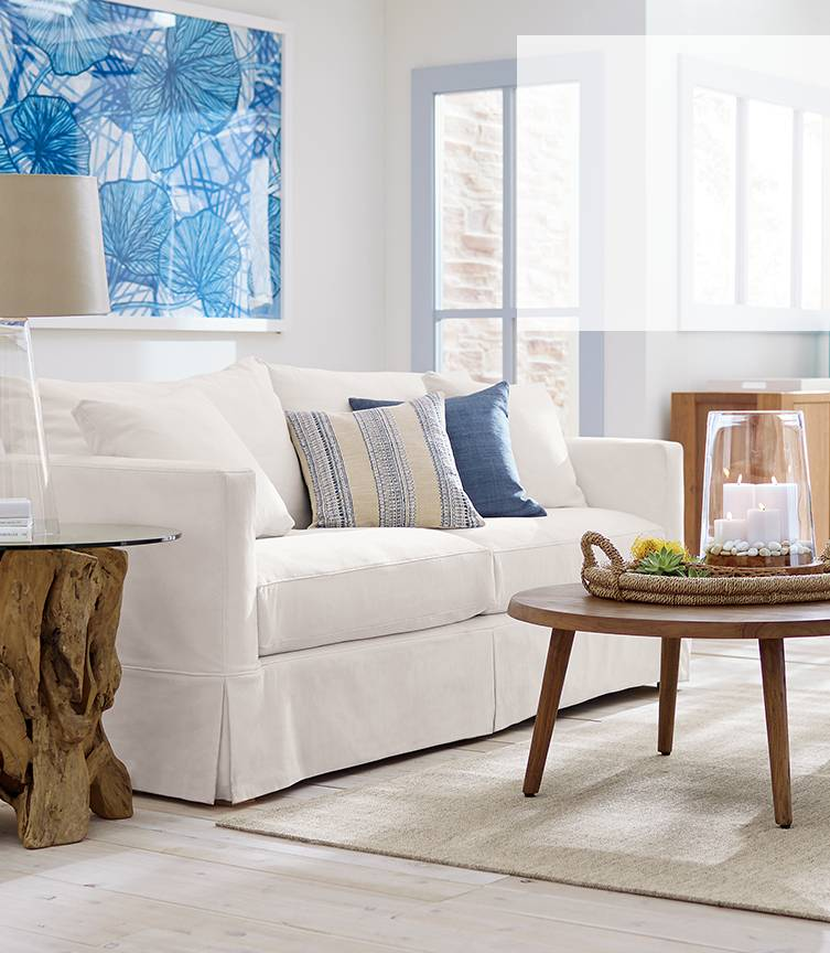 A casual living room with a white slipcovered Willow sofa, next to a driftwood side table and round edgewood table.