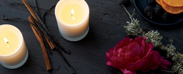 Two flickering candles on a black surface surrounded by flowers, dried oranges, and other fragrant herbs.