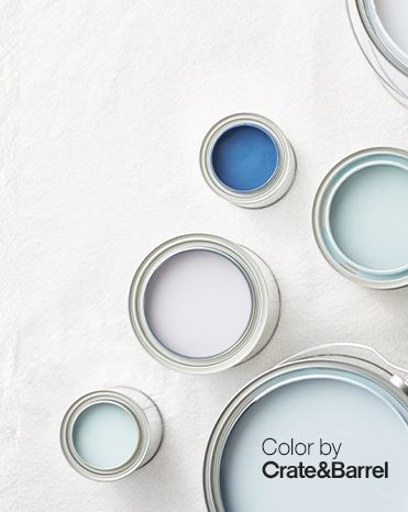 Overhead view of paint cans filled with white, blue, and light blue paint.