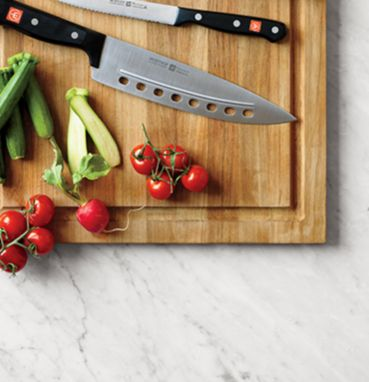 Wusthof knives  and some tomatoes on a wooden cutting board on top of a marble kitchen counter.