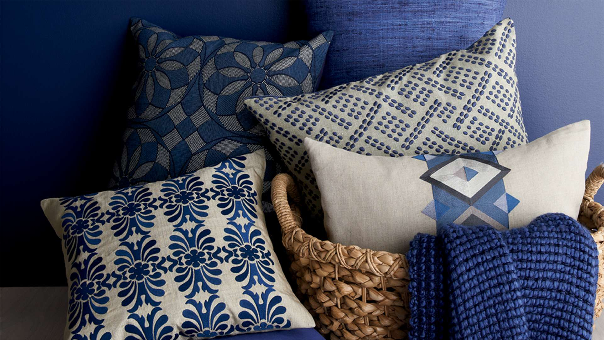 Blue pillows and throws in a basket