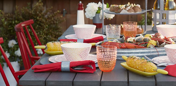 Outdoor table set with red-themed dinnerware.
