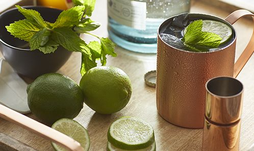 Making a moscow mule with lime, vodka and, not pictured, ginger beer. Moscow Mule mug on tray with limes, jigger, and vodka