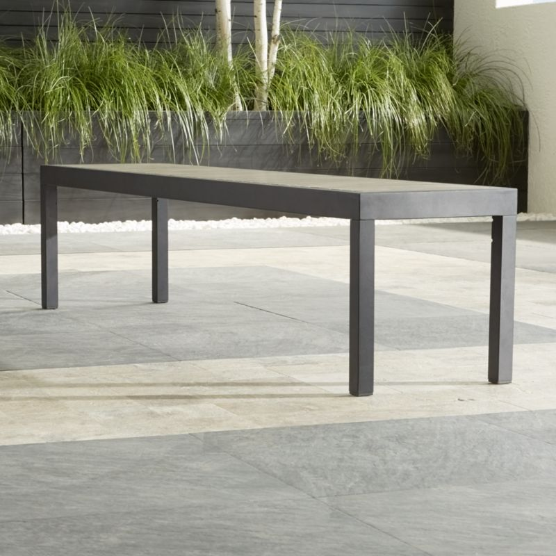 Our stylish Alfresco outdoor dining collection features this casual bench that fools the eye with the look of real wood as it fools the elements with UV- and fade-resistant qualities. Innovative warm grey faux wood slats are treated with UV and anti-oxidant protection. <NEWTAG/><ul><li>Extruded polystyrene with UV and anti-oxidant protection</li><li>Aluminum frame with powdercoat finish</li><li>Seats 4</li><li>Made in China</li></ul><br />