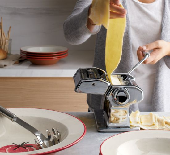 A woman feeds a sheet of pasta dough through a pasta machine