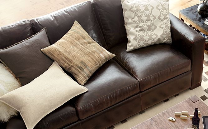 Axis brown leather sofa with beige pillows