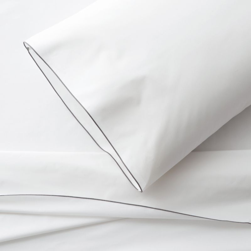 Clean, basic white bedding upgrades in soft, smooth cotton percale, beautifully contrasted with a graceful grey overlocking stitch on the flat sheet and pillow case. Generous fitted sheet pockets accommodate thicker mattresses. Sheet set includes one flat sheet, one fitted sheet and one standard pillow case. Bed pillows also available.<br /><br />This product is certified by Oeko-Tex®, an international association focused on textile safety and sustainable production. Oeko-Tex® tests for known harmful substances and chemicals as well as for acidity and color fastness. All components of the product must comply with stringent Oeko-Tex® standards to achieve certification.<br /><br /><NEWTAG/><ul><li>Certified by Oeko-Tex</li><li>100% cotton percale</li><li>200-thread-count</li><li>Machine wash; tumble dry low</li><li>Made in Portugal</li></ul>