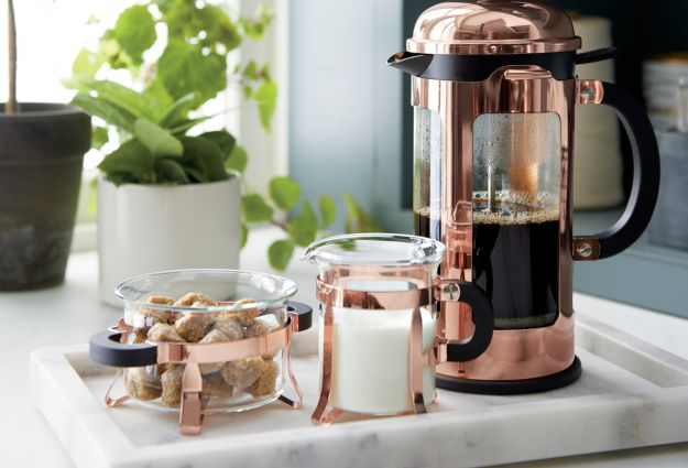 Copper Bodum coffee press on a marble serving tray with a matching copper cream and sugar set