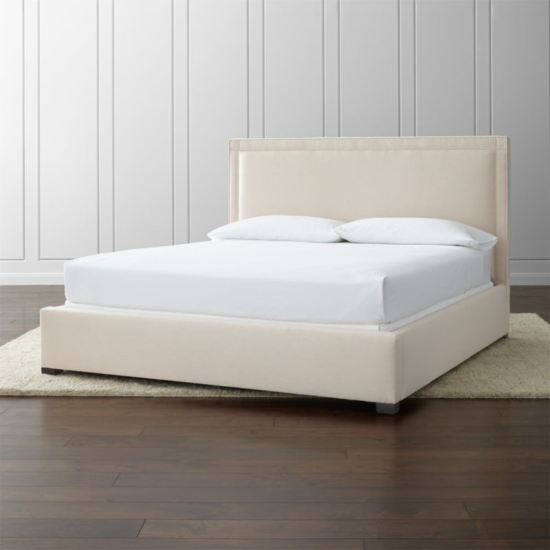 The square sensibility and architectural polish of our Border bed take the edge off in a soft neutral cotton-poly blend over the linear frame. Self-welt detailing outlines the perimeter of the king bed, with horizontal and vertical lines that intersect at each corner. <NEWTAG/><ul><li>Frame is benchmade with certified sustainable hardwood that's kiln-dried to prevent warping</li><li>Soy-based polyfoam cushioning</li><li>Solid maple legs with brown finish</li><li>3 metal slats with 3 center support legs</li><li>Accommodates mattress and box spring (sold separately)</li><li>Maximum weight capacity: 800 lbs. (includes weight of mattress, box spring and occupants)</li><li>Made in North Carolina, USA</li></ul><br />