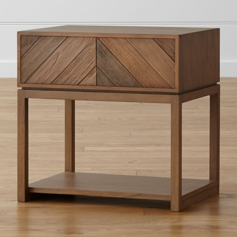 Crafted by master woodworkers in Indonesia, the Chevron nightstand's striking inlaid veneer of sustainable Mindi wood sets a geometric backdrop in the bedroom, naturally highlighting the rich textures and warm shading of this hardwood. <NEWTAG/><ul><li>Mindi wood veneer over engineered wood</li><li>Natural color stain, water-based topcoat and sealer (color variances to be expected)</li><li>Beveled drawer fronts with integrated pulls</li><li>Solid mahogany legs</li><li>Self-closIng metal undermount drawer glides</li><li>Made in Indonesia</li></ul>