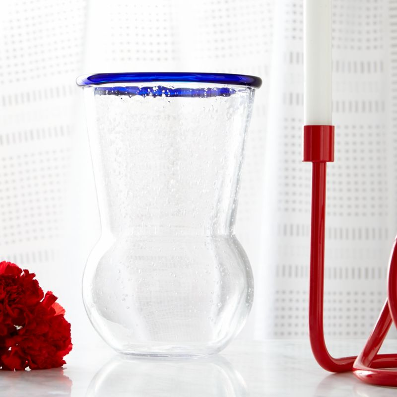 Paola Navone's palette of blues is inspired by her world experiences and life by the sea. From the deep blues found in Moroccan tiles and the Turkish eye to the aquamarine seas of the Greek Isles, a range of blues infuses the Como collection with coastal color and flair. Tulip-shaped vase bubbles like the tide, handcrafted of thick, clear glass and rimmed with a ring of cobalt.<br /><br /><NEWTAG/><ul><li>Designed by Paola Navone exclusively for Crate and Barrel</li><li>Handcrafted</li><li>Glass</li><li>Hand wash</li><li>Made in Thailand</li></ul>