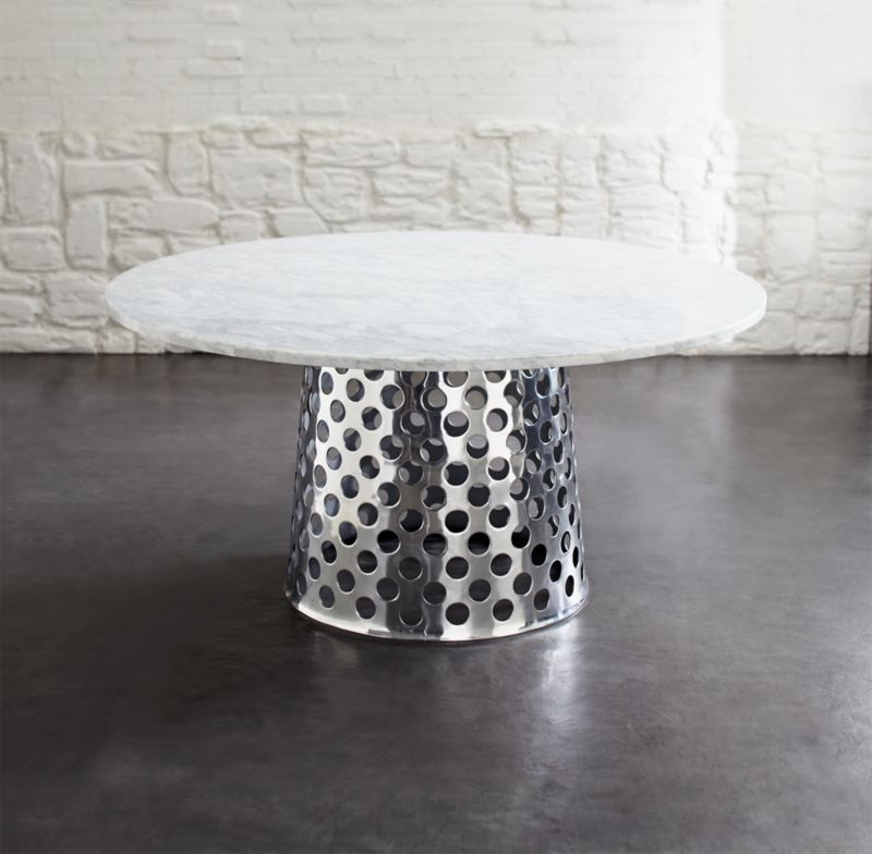 Paola Navone's unique and unexpected furnishings are simple, elegant and immediately familiar, with a livable look that blends with any style. Bold perforated circles pattern aluminum base topped with gorgeous Italian Carrara marble in an eclectic mix of handworked metal and natural stone. Crafted for us exclusively in Mumbai, each round base is crafted of a single sheet of aluminum that is die-cut, welded and polished to a gleaming mirror finish. Solid 8mm marble top displays the unique markings and color variations of pure, unfinished marble and is built around an aluminum honeycomb interior to provide lightweight support and minimize the chances of breakage.  A clean, modern pedestal table, generously proportioned for gathering friends and family.<br /><br /><NEWTAG/><ul><li>Designed by Paola Navone exclusively for Crate and Barrel</li><li>Handcrafted</li><li>Unfinished and polished Italian Carrara marble</li><li>Honeycomb tabletop construction</li><li>Aluminum base</li><li>Seats 6</li><li>Bolt and screw joinery</li><li>For indoor or protected outdoor use</li><li>Made in China and India</li></ul>