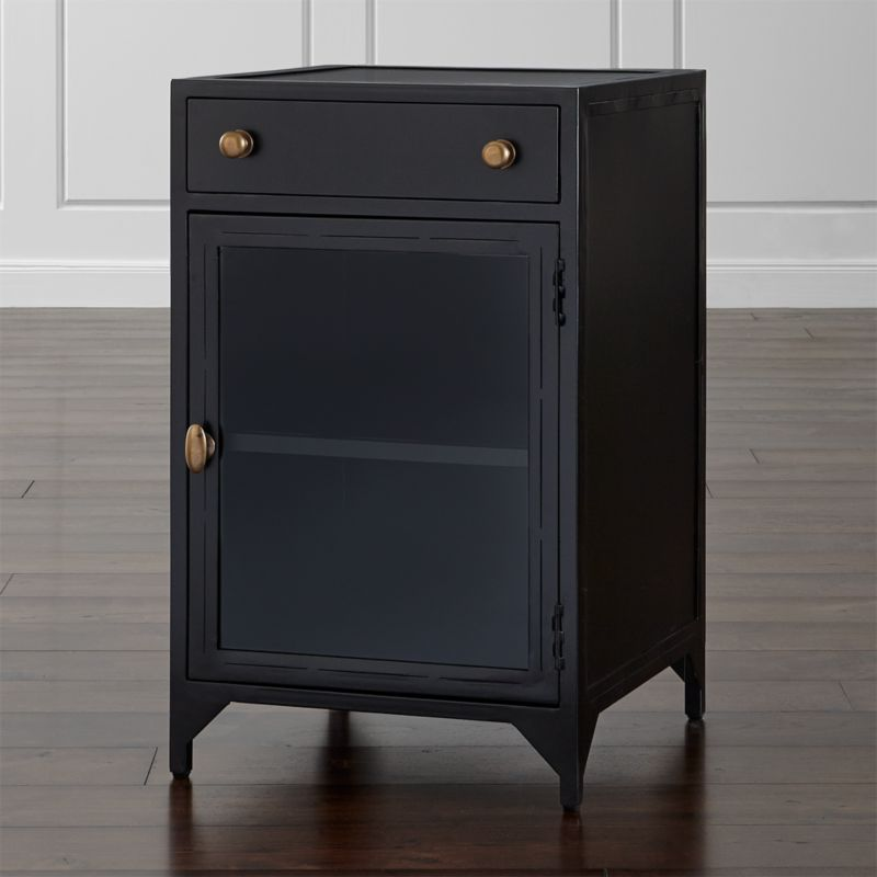 Iron takes a decorative turn in this finely-crafted nightstand with traditional, clean lines. Crafted from hand-cut, sanded and welded iron, Cortina's sleek, dark silhouette features an upper drawer for storage. Below, a glass door opens to the left to reveal a generous interior shelf. <NEWTAG/><ul><li>Hand welded iron with clear lacquer topcoat</li><li>Glass door with handle on left</li><li>Antique brass pulls</li><li>Metal drawer glides</li><li>Levelers</li><li>Made in Vietnam</li></ul>
