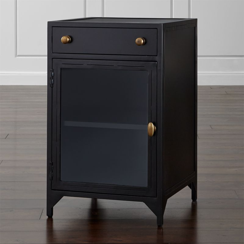 Iron takes a decorative turn in this finely-crafted nightstand with traditional, clean lines with an industrial nod. Cortina nightstand's sleek, dark silhouette, crafted from hand-cut, sanded and welded iron, features an upper drawer for storage. Below, a glass door opens to the right, revealing a generous interior shelf. <NEWTAG/><ul><li>Hand welded iron with clear lacquer topcoat</li><li>Glass door with handle on right</li><li>Antique brass pulls</li><li>Metal drawer glides</li><li>Levelers</li><li>Made in Vietnam</li></ul>