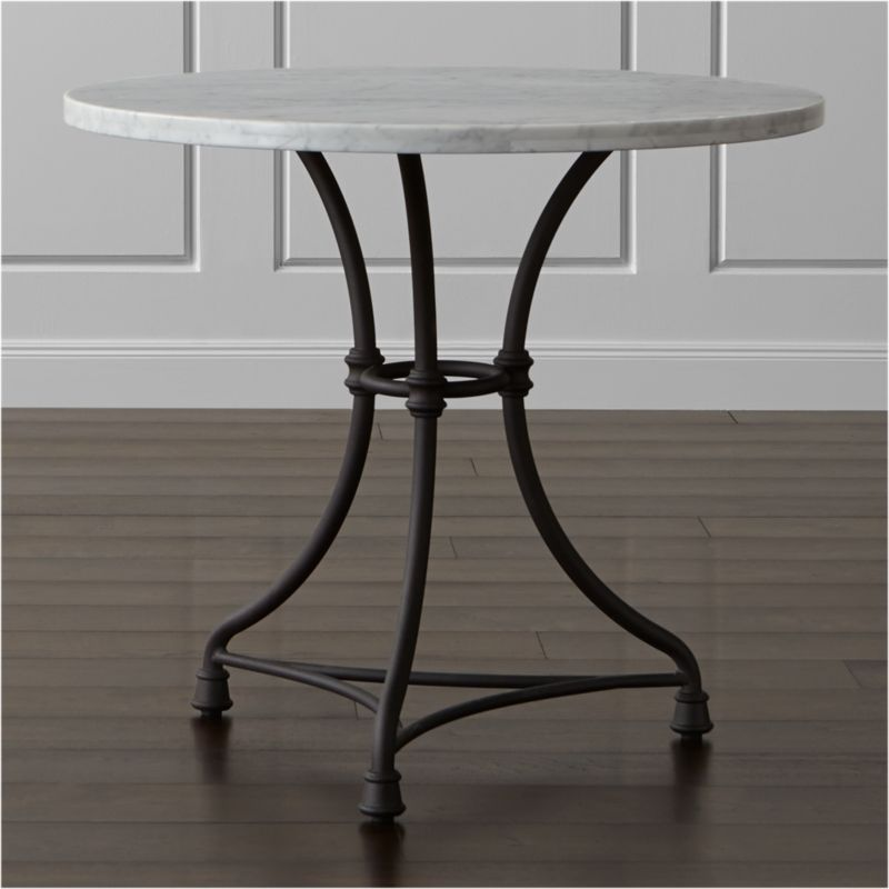Elegant marble-top table translates French style into a timeless design that evokes the charm of an Old World pastry shop. Practical and beautiful, the white marble top sits on a classically inspired metal base streamlined for today. <NEWTAG/><ul><li>Carrara marble top over engineered wood</li><li>Cast steel and aluminum base with antiqued hand-finish</li><li>Color and natural veining will vary with each unique top</li><li>Protective floor glides</li><li>Seats two</li><li>Made in China</li></ul><br />