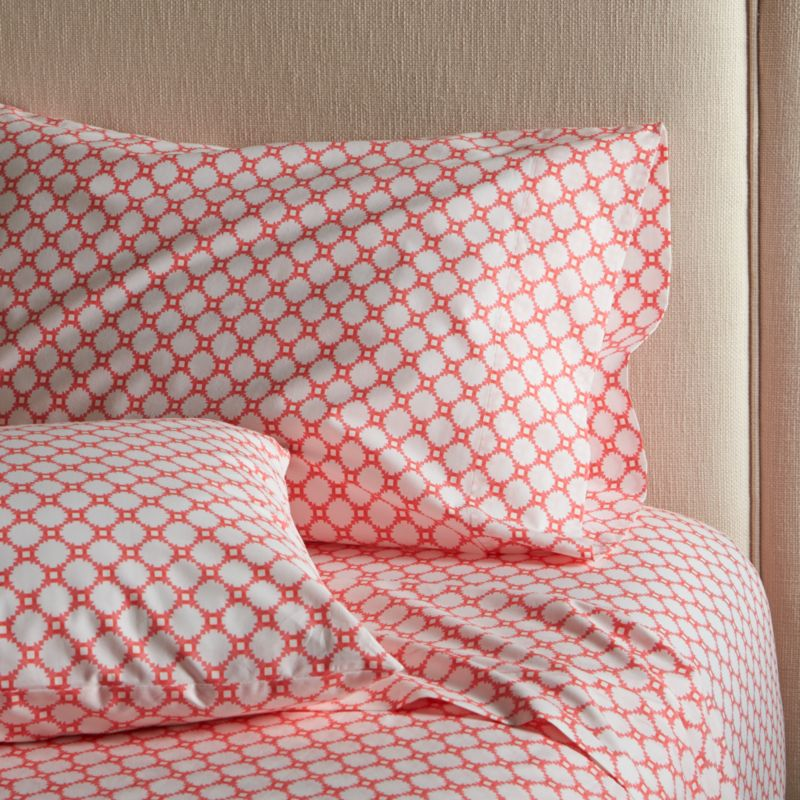 Classic geometric quilting pattern updates in sunny coral and white as a sunny, streamlined graphic by London designer Genevieve Bennett, printed on soft cotton percale. Scaled-down motif coordinates beautifully with boldly patterned Genevieve bed linens. Sheet set includes one flat sheet, one fitted sheet and two king pillow cases. Bed pillows also available.<br /><br /><NEWTAG/><ul><li>Designed by Genevieve Bennett</li><li>100% cotton percale</li><li>200-thread-count</li><li>Machine wash cold, tumble dry low; warm iron as needed</li><li>Made in Portugal</li></ul>
