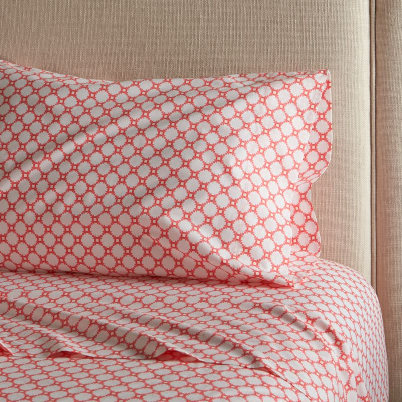 Classic geometric quilting pattern updates in sunny coral and white as a sunny, streamlined graphic by London designer Genevieve Bennett, printed on soft cotton percale. Scaled-down motif coordinates beautifully with boldly patterned Genevieve bed linens. Sheet set includes one flat sheet, one fitted sheet and one standard pillow case. Bed pillows also available.<br /><br /><NEWTAG/><ul><li>Designed by Genevieve Bennett</li><li>100% cotton percale</li><li>200-thread-count</li><li>Machine wash cold, tumble dry low; warm iron as needed</li><li>Made in Portugal</li></ul>