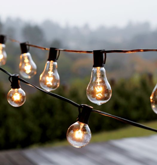 Illuminated globe bulb hanging patio string lights over an outdoor deck
