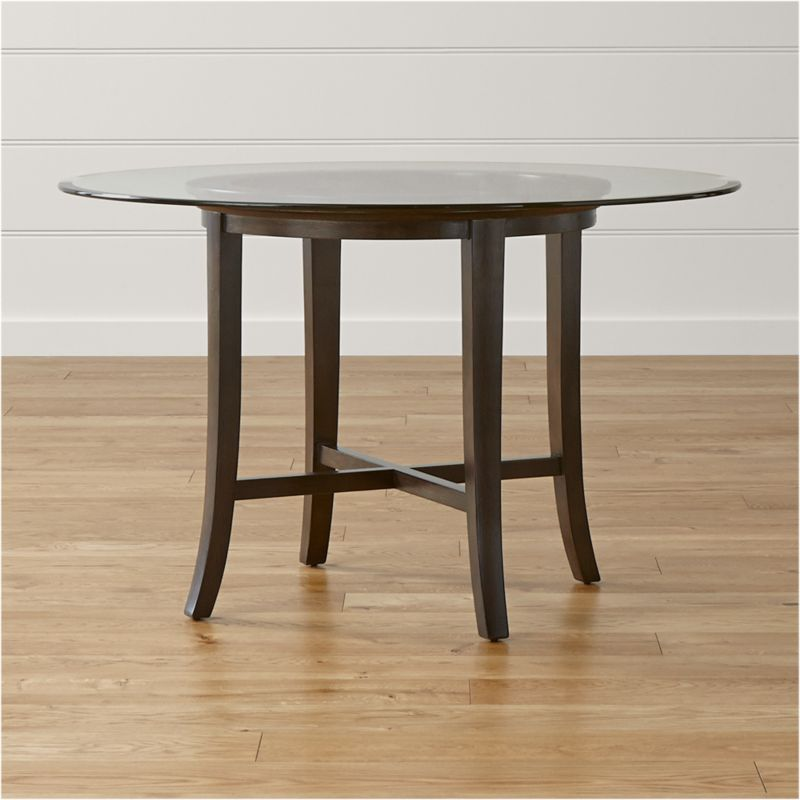 "With its distinctive ""halo"" effect, this striking table features a flat glass top with a deep, light-refracting reverse bevel that's echoed in the open ring of the solid chestnut wood base. Featuring a cross brace and slightly flared legs, the table is constructed using traditional wood-on-wood joinery without the use of screws or nails. <NEWTAG/><ul><li>Solid chestnut base with deep ebony finish</li><li>Clear ½""-thick glass top with reverse bevel and polished edge</li><li>BreathingJoinery ™</li><li>Plastic glides</li><li>Seats 4</li><li>Made in China</li></ul>"