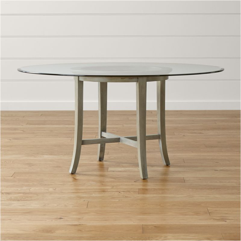"""With its distinctive """"halo"""" effect, this striking table features a flat glass top with a deep, light-refracting reverse bevel that's echoed in the open ring of the solid chestnut wood base. Featuring a cross brace and slightly flared legs, the table is constructed using traditional wood-on-wood joinery without the use of screws or nails. <NEWTAG/><ul><li>Solid chestnut base with grey-washed lacquer finish</li><li>Clear ½""""-thick glass top with reverse bevel and polished edge</li><li>BreathingJoinery ™</li><li>Plastic glides</li><li>Seats 6</li><li>Made in China</li></ul>"""