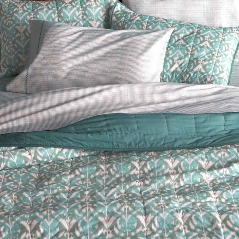 Gorgeous tones of blue and green overlap in a modern ikat pattern on soft, 100% cotton. Lightweight yet cozy quilt is hand quilted and reverses to solid aqua. -Hand-quilted<br /><ul><li>100% cotton</li><li>100% cotton fill</li><li>Machine wash, tumble dry low; warm iron as needed</li><li>Made in India</li></ul><NEWTAG/>