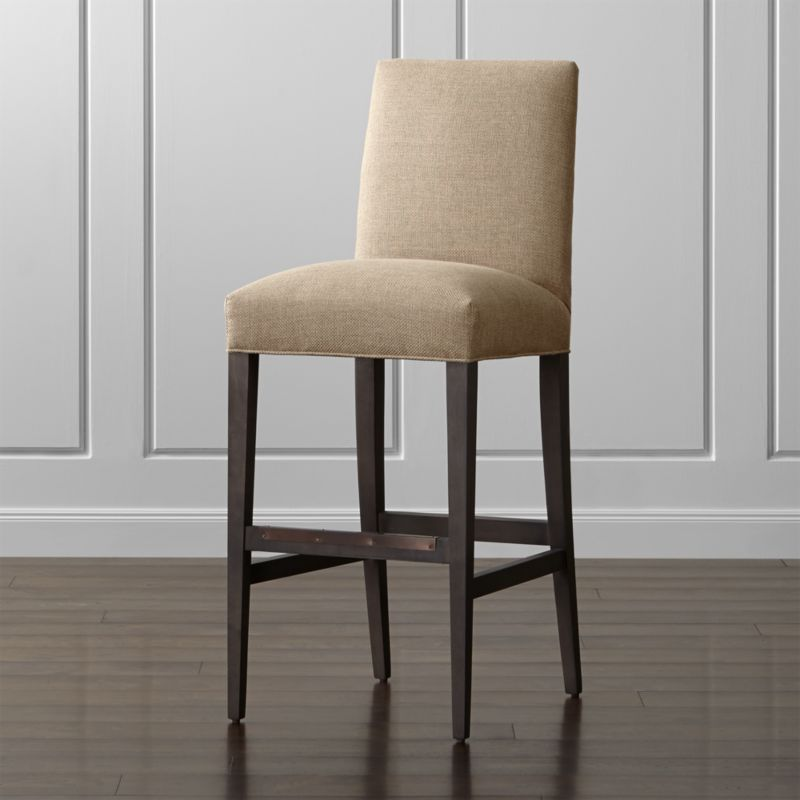 Sit tall with the classic, polished proportions and casual formality of our scaled-up Miles bar stool. Sized especially for the bar, this taller stool features a comfortably padded tight seat and back upholstered in a durable synthetic fabric. The hardwood legs with a warm grey finish taper gracefully to the floor, with the added benefit of a convenient footrest. The Miles Bar Stool is a Crate and Barrel exclusive.<br /><br /><NEWTAG/><ul><li>Certified-sustainable solid hardwood frame</li><li>Soy-based polyfiber tight seat and tight back</li><li>Solid hardwood legs with a warm grey finish</li><li>Plastic glides</li><li>Made in North Carolina, USA</li></ul>