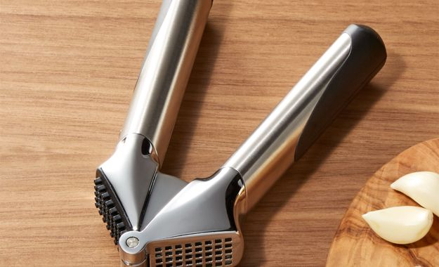 OXO steel garlic press on a wood cutting board next to a pinch of minced garlic and two peeled garlic cloves